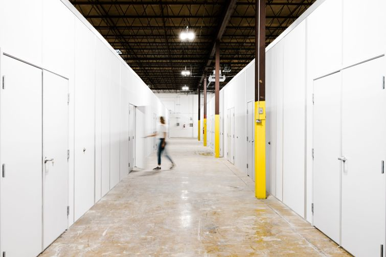 A hallway with storage sheds on either side.