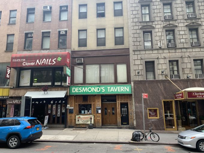 A grey storefront of an Irish Bar with a large green sign, named Desmond's Tavern.