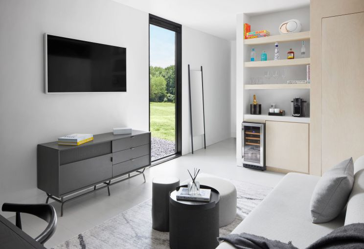 """The 400-square-foot rooms feature modular furniture, king-size beds, a small living room furniture setup with a 55"""" television, and a small wine fridge."""