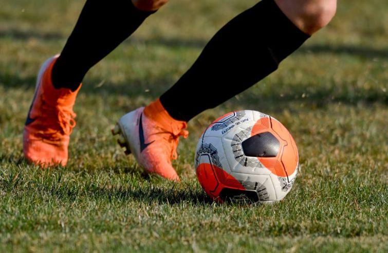A detail photo of a player's feet dribbling a soccer ball.