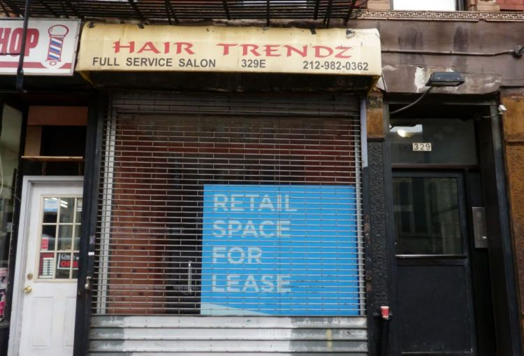 """A blue """"Retail Space for Lease"""" sign sits in a gated storefront formerly belonging to Hair Trendz."""