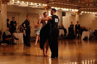 Two dancers, a woman in a black dress and a man in a vest, in Grand Prospect hall in 2011.
