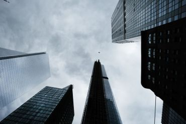 An upwards view towards the tops of several skyscrapers in New York City backed by a cloudy grey sky.
