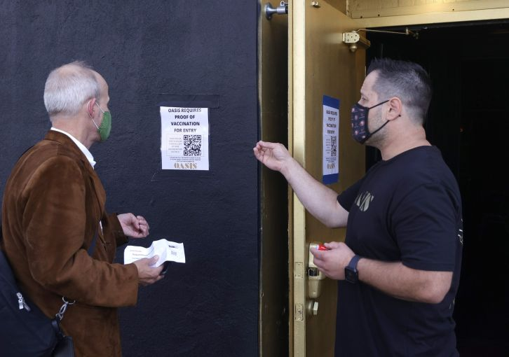 A doorman at Oasis informs a customer that a vaccination card is required to enter the club.