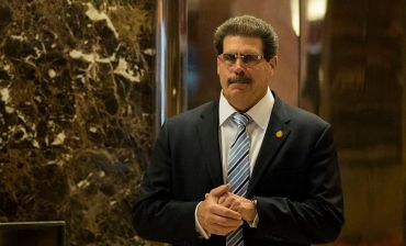 Matthew Calamari walks down a hallway with marble walls in sunglasses and a suit.