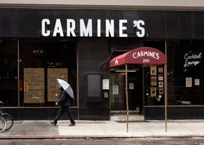 A person holds an umbrella outside Carmine's Italian Restaurant in Times Square