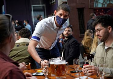 A hospitality worker serves a pitcher of beer to customers sat at an outdoor table of a re-opened bar.