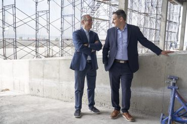 Two men standing in a warehouse.