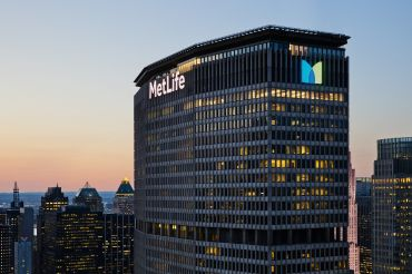 """The top of a large skyscraper with the word """"MetLife"""" in glowing letters on the top."""