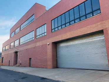 A large red brick warehouse with a garage.