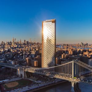 A large silver condo building rises above the Manhattan Bridge backed by a clear blue sky.