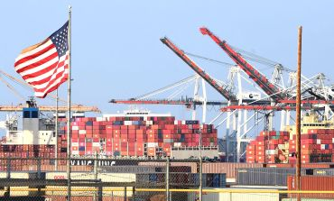 A US flag flies near containers stacked high on a cargo ship at the Port of Los Angeles on September 28 in Los Angeles. A record number of cargo ships are stuck floating and waiting off the southern California coast amid a supply chain crisis which could mean fewer gifts and toys for Christmas this year as a combination of growing volumes of cargo, Covid-19 related safety measures and a labor shortage slow the handling and processing of cargo from each ship.