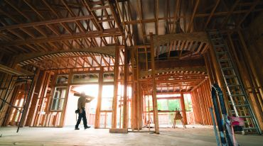 A large, spacious wooden structure with a worker walking through it.