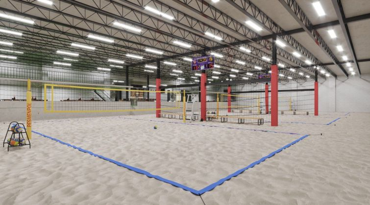 An indoor beach volleyball court with sand and nets.