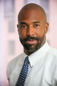 A bearded man in a tie looking into the camera.